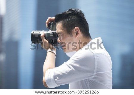 Portrait of happy Chinese man taking photos with a camera in the city. Asian Photographer shooting outside with digital camera.
