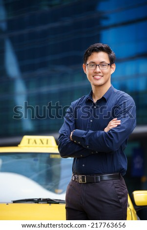 Portrait of happy chinese taxi driver leaning on yellow car with arms crossed, smiling and looking at camera - stock photo
