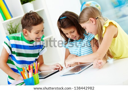 Portrait of happy classmates at workplace using digital tablets - stock photo