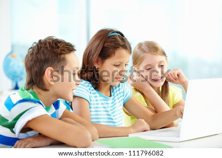 Portrait of happy classmates at workplace using laptop at lesson - stock photo