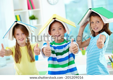 Portrait of happy classmates with books on their heads keeping thumbs up - stock photo
