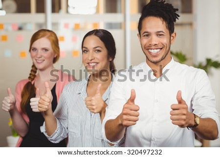 Portrait of happy colleagues showing thumbs up at office - stock photo