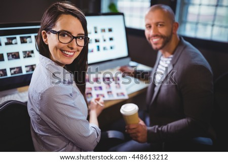 Portrait of happy colleagues sitting at computer desk in creative office - stock photo
