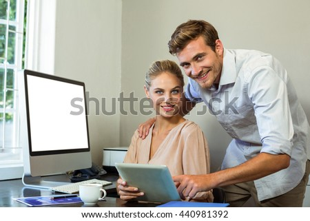 Portrait of happy colleagues using digital tablet at desk in office - stock photo