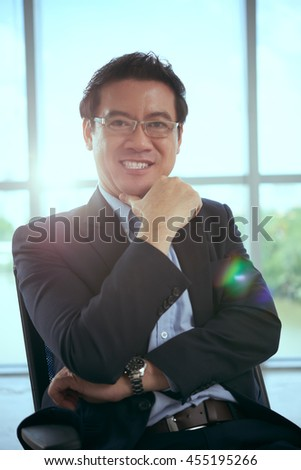 Portrait of happy confident ceo sitting on his chair