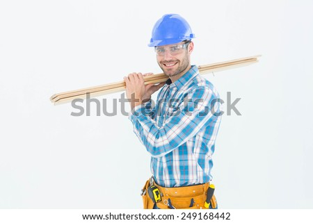 Portrait of happy construction worker carrying wooden planks against white background - stock photo