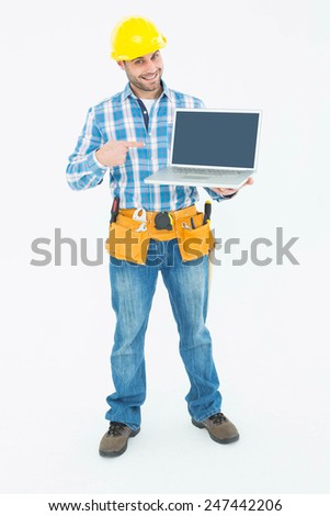 Portrait of happy construction worker pointing at laptop against white background - stock photo