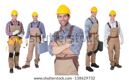 Portrait of happy construction worker standing in front of his team. Isolated on white - stock photo