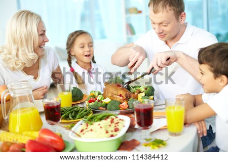 Portrait of happy couple and their children sitting at festive table and going to eat roasted turkey - stock photo