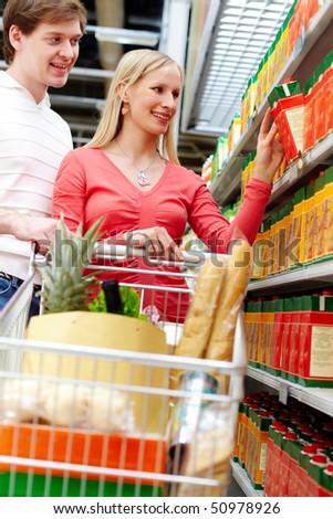 Portrait of happy couple choosing pack of juice in supermarket - stock photo