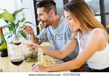 Portrait of happy couple dining and drink wine at home.