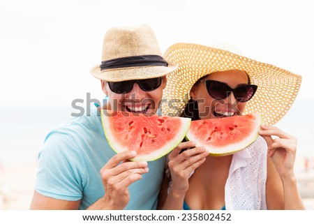 portrait of happy couple enjoying watermelon on summer holiday - stock photo