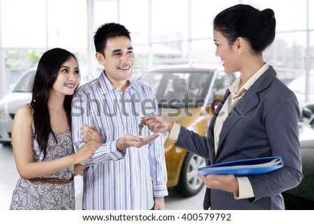 Portrait of happy couple get a car key from a car dealer in the showroom - stock photo