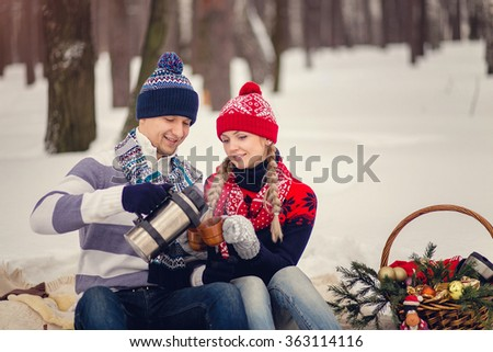 Portrait of happy couple going to drink hot tea on winter day.