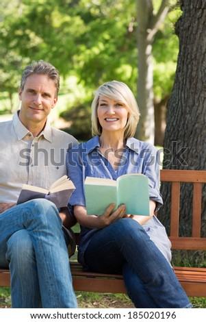 Portrait of happy couple holding books while sitting on park bench - stock photo