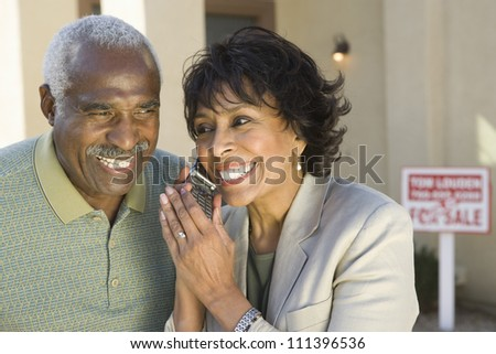 Portrait of happy couple holding cell phone in front on new house - stock photo