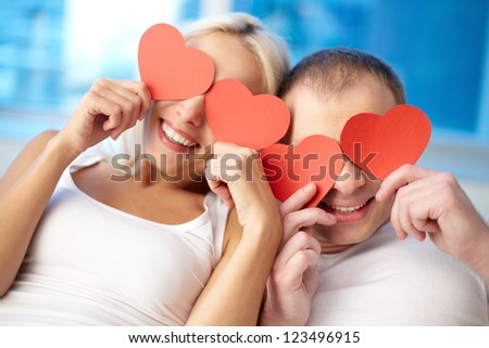 Portrait of happy couple holding red paper hearts by their eyes
