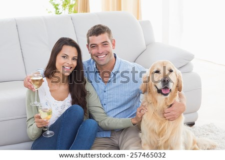 Portrait of happy couple holding wine glasses while sitting with dog at home - stock photo