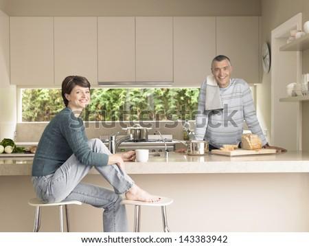 Portrait of happy couple in kitchen - stock photo