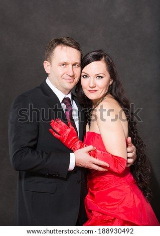 Portrait of happy couple in love posing at studio on gray background dressed in red. Attractive man and woman. - stock photo