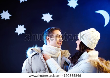 Portrait of happy couple looking at one another with moon and stars above their heads - stock photo