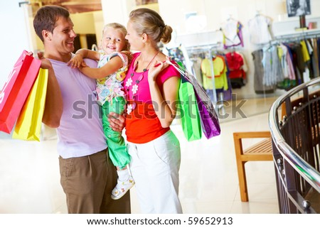 Portrait of happy couple looking at their daughter in the mall - stock photo