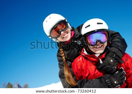 Portrait of happy couple of snowboarders outside during winter vacations