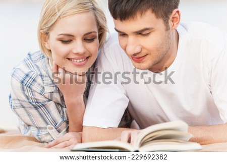 Portrait Of Happy Couple Reading Book On Summer Beach. Couple reading book on lake shore - stock photo
