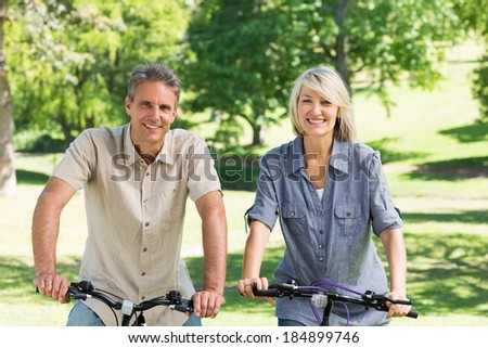 Portrait of happy couple riding bicycles in park - stock photo