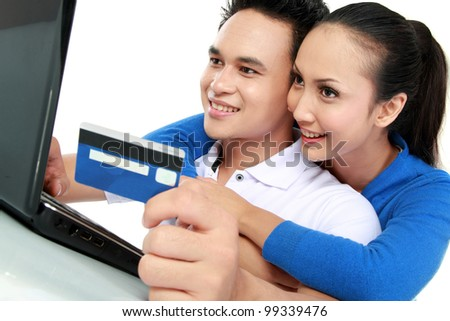 portrait of happy couple shopping online using credit card - stock photo