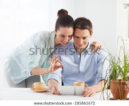 Portrait of happy couple shopping online using digital tablet - stock photo
