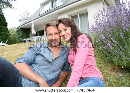 Portrait of happy couple sitting in front of their new house - stock photo