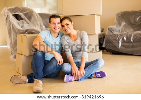 portrait of happy couple sitting in new house - stock photo