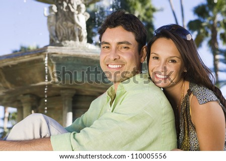 Portrait of happy couple sitting with fountain in the background