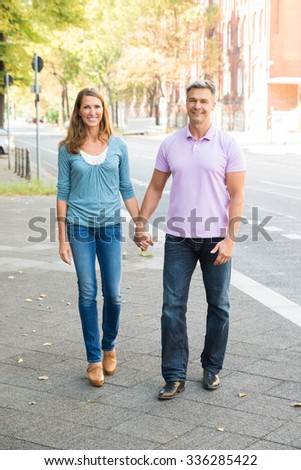 Portrait Of Happy Couple Walking On The Street - stock photo