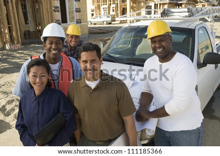 Portrait of happy couple with group of architects at construction site - stock photo