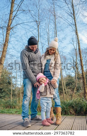 Portrait of happy couple with her little daughter enjoying together leisure over a wooden pathway into the forest. Family time concept. - stock photo
