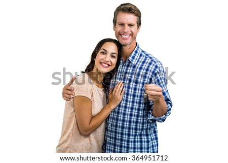 Portrait of happy couple with keys standing against white background