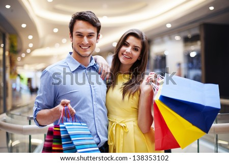 Portrait of happy couple with shopping bags  - stock photo