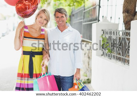 Portrait of happy couple with shopping bags and balloons in city - stock photo