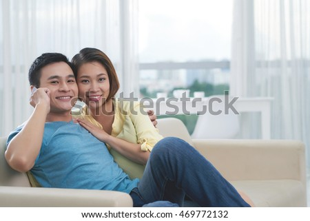 Portrait of happy couple with smartphone at home