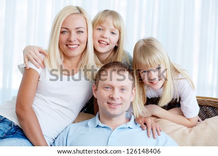 Portrait of happy couple with twin daughters resting at home