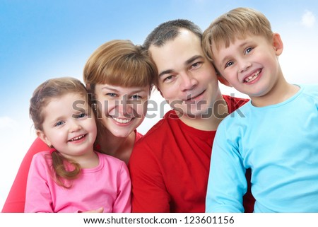 Portrait of happy couple with two children of blue sky background - stock photo