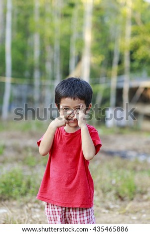Portrait of happy cute Asian Thai little boy shy expression covering his face with hands outdoor - stock photo