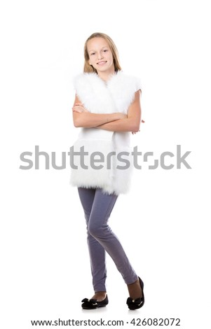 Portrait of happy cute beautiful blond girl wearing white furry vest, holding her arms folded, posing, friendly smiling, isolated studio, white background, full length - stock photo