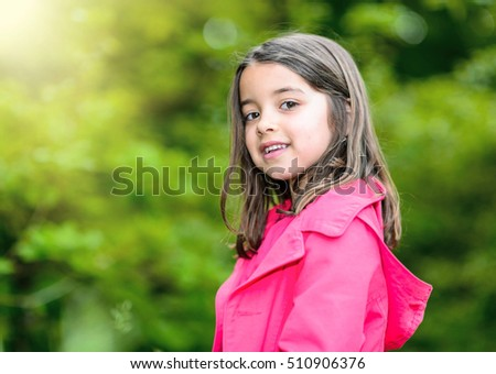 portrait of happy cute child with flower garden on background