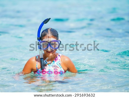 Portrait of happy cute girl wearing snorkeling mask ready to dive in the sea