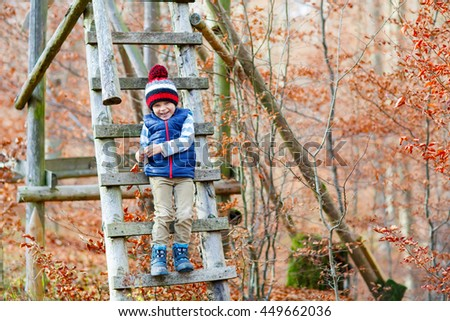 Portrait of happy cute little kid boy with autumn leaves background in colorful clothing. Funny child having fun in fall forest or park on cold day. - stock photo