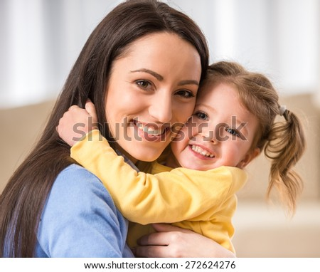Portrait of happy daughter and her mother are smiling at the camera. - stock photo