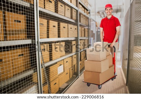Portrait of happy delivery man pushing cart full of cardboard boxes in warehouse - stock photo